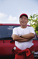 A man with a red van smiles at the camera as he works - Asia Images Group