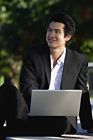 A man uses his laptop in the park - Asia Images Group