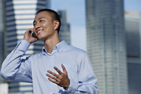 A man talks on his cellphone outdoors - Asia Images Group