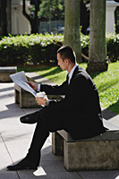 A man sits and reads the newspaper in the park - Asia Images Group