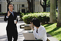 Two men wave at each other in the park - Asia Images Group