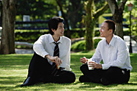 Two men eat their lunch together in the park - Asia Images Group