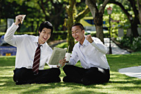 Two men get excited as they read the newspaper in the park - Asia Images Group