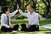 Two men eat their lunch together in the park and high five - Asia Images Group