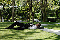 A man lies down and has a rest in the park - Asia Images Group