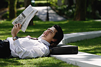 A man lies down and reads the newspaper in the park - Asia Images Group