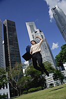 A man jumps in the air with his laptop - Asia Images Group