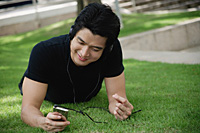 A man listens to music on a mp3 player in the park - Asia Images Group