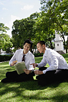 Two men read the newspaper in the park - Asia Images Group
