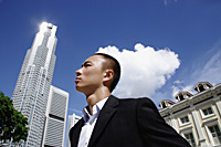 A man in a suit with a skyscraper behind him - Asia Images Group