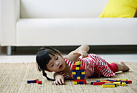 A small girl plays with blocks on the floor - Asia Images Group