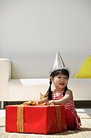 A young girl unwraps a birthday present - Asia Images Group