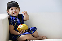 A small girl in blue silk cheongsam plays with a piggy bank - Asia Images Group