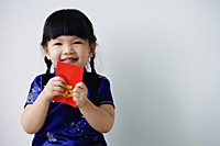A small girl holds a red packet as she looks at the camera - Asia Images Group