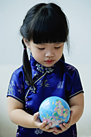 A small girl in blue silk cheongsam holds a globe - Asia Images Group