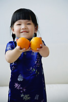 A small girl holds out two mandarin oranges - Asia Images Group