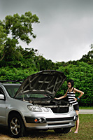 A woman checks under the hood of her car - Asia Images Group