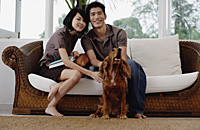 A young couple with a dog look at the camera - Asia Images Group