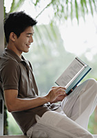 A man smiles as he reads a book - Asia Images Group