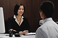 A woman sits at her desk while she talks with a man - Asia Images Group
