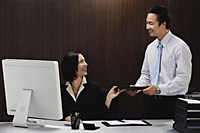 A woman sits at her desk while she talks with a man at work - Asia Images Group