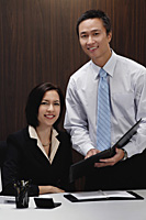 A man and a woman smile at the camera while they are at work - Asia Images Group