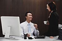 A man sits at his desk while he talks with a woman at work - Asia Images Group