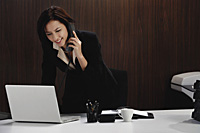 A woman talks on the phone while she is at her desk - Asia Images Group