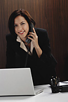 A woman looks at the camera while she talks on the phone at work - Asia Images Group