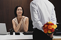 A man brings a woman flowers while she is at work - Asia Images Group
