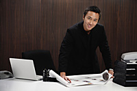A man smiles at the camera as he rolls out plans on his desk - Asia Images Group