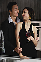 A couple smile at each other while in the kitchen - Asia Images Group