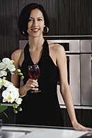 A woman smiles at the camera holding a glass of red wine - Asia Images Group