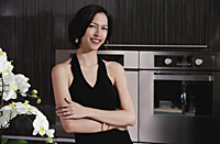 A woman smiles at the camera in the kitchen - Asia Images Group