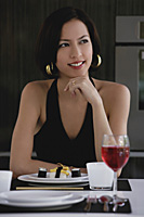 A woman sits at a table with a plate of sushi and a glass of red wine - Asia Images Group