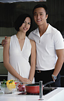 A couple smile at the camera as they stand in the kitchen - Asia Images Group