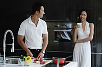 A couple prepare dinner together in the kitchen - Asia Images Group