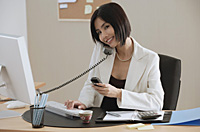 A woman talks on the phone while she is at work - Asia Images Group
