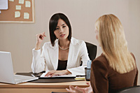 Two woman talk together at work - Asia Images Group
