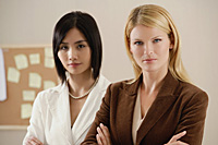 Two female colleagues look at the camera together - Asia Images Group