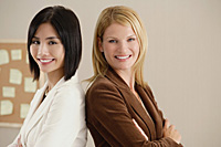 Two female colleagues smile at the camera together - Asia Images Group