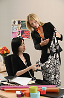 Two female colleagues look at a dress while at work - Asia Images Group