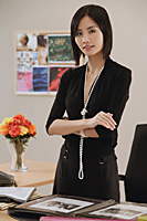 A woman stands behind her desk as she looks at the camera - Asia Images Group