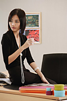 A woman sits on her desk at work - Asia Images Group