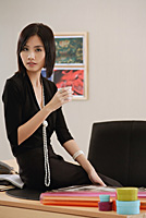 A woman sits on her desk while she looks at the camera - Asia Images Group