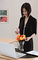 A woman tends to a vase of flowers on her desk at work - Asia Images Group