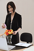 A woman smiles at the camera as she tends to a vase of flowers on her desk at work - Asia Images Group