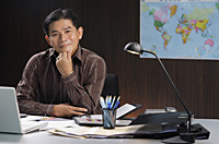 A man smiles at the camera as he sits at his desk - Asia Images Group