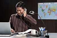 A man talks on the phone as he works - Asia Images Group