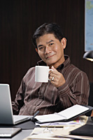 A man having a drink while working at his desk - Asia Images Group